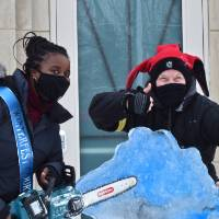 person holding chainsaw, person with thumbs up, and michigan ice sculpture